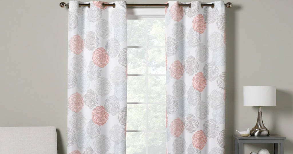 two curtain panels with grey, blue, and red dot print hanging on curtain rod in front of window