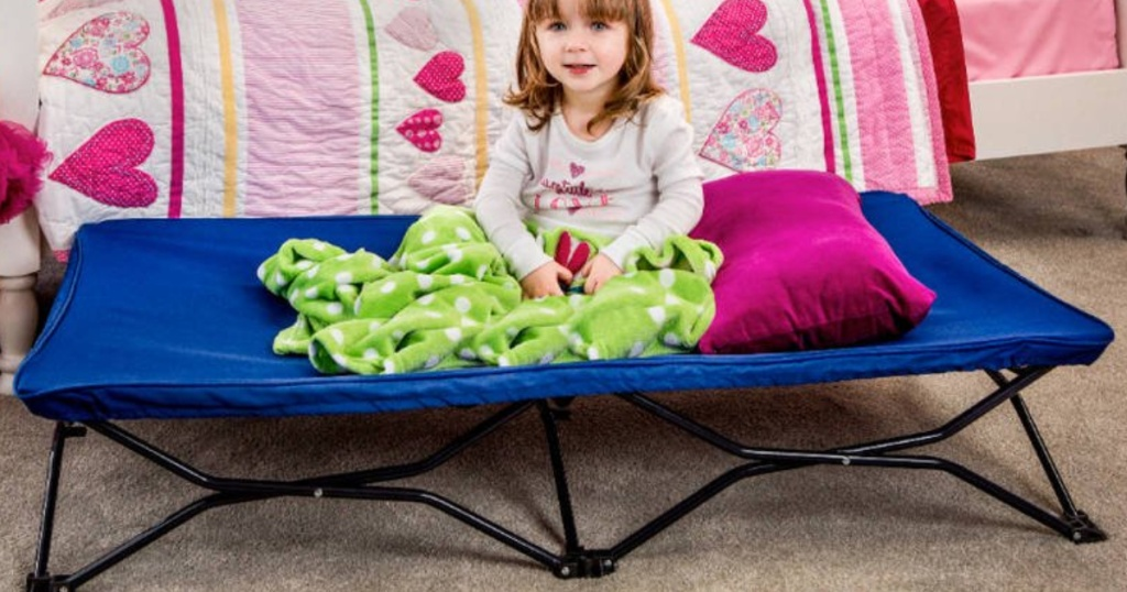 little girl wearing pajamas sitting on a blue toddler size cot