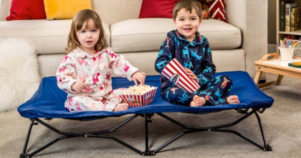 2 small children wearing pajamas sitting on a toddler cot