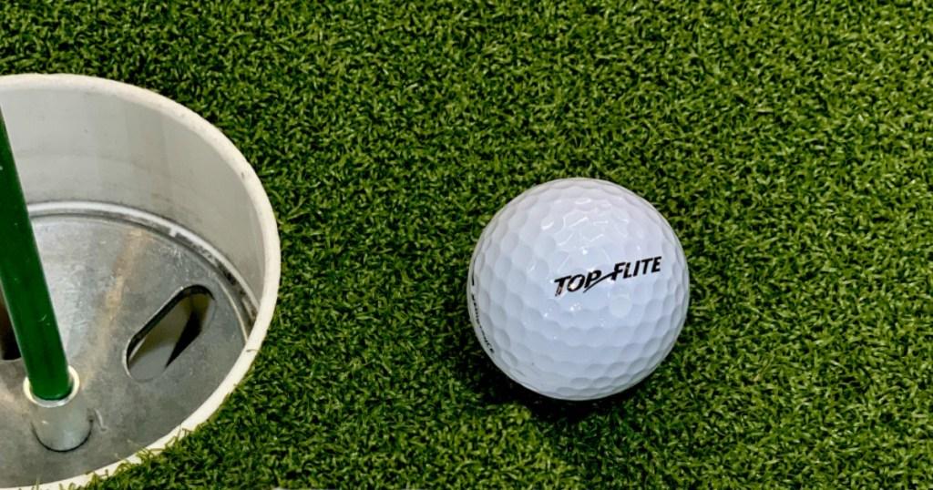 golf ball next to golf hole