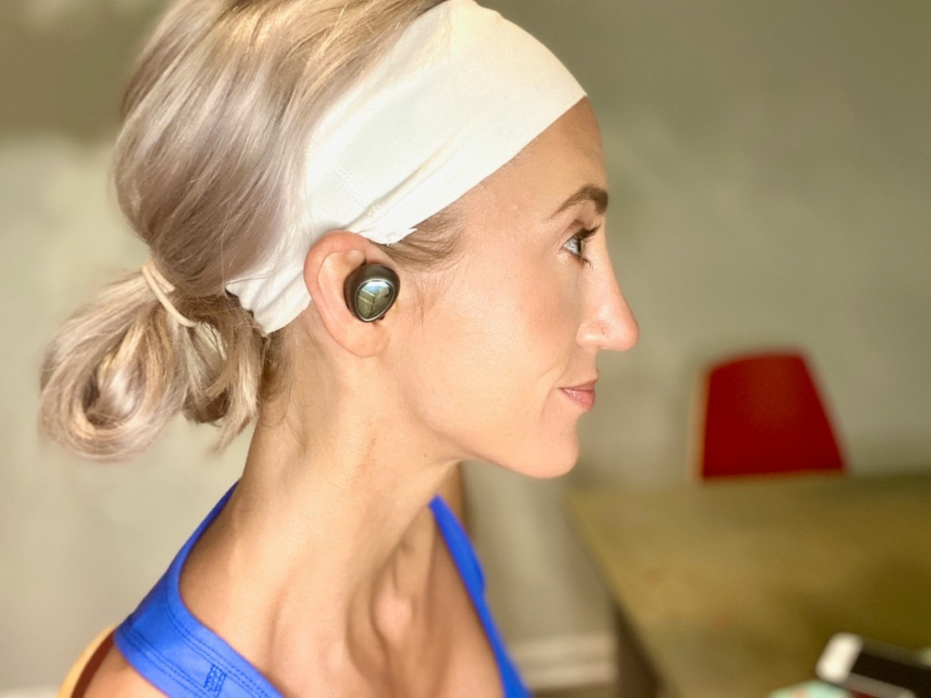 woman with hair pulled back and headband on wearing earbuds