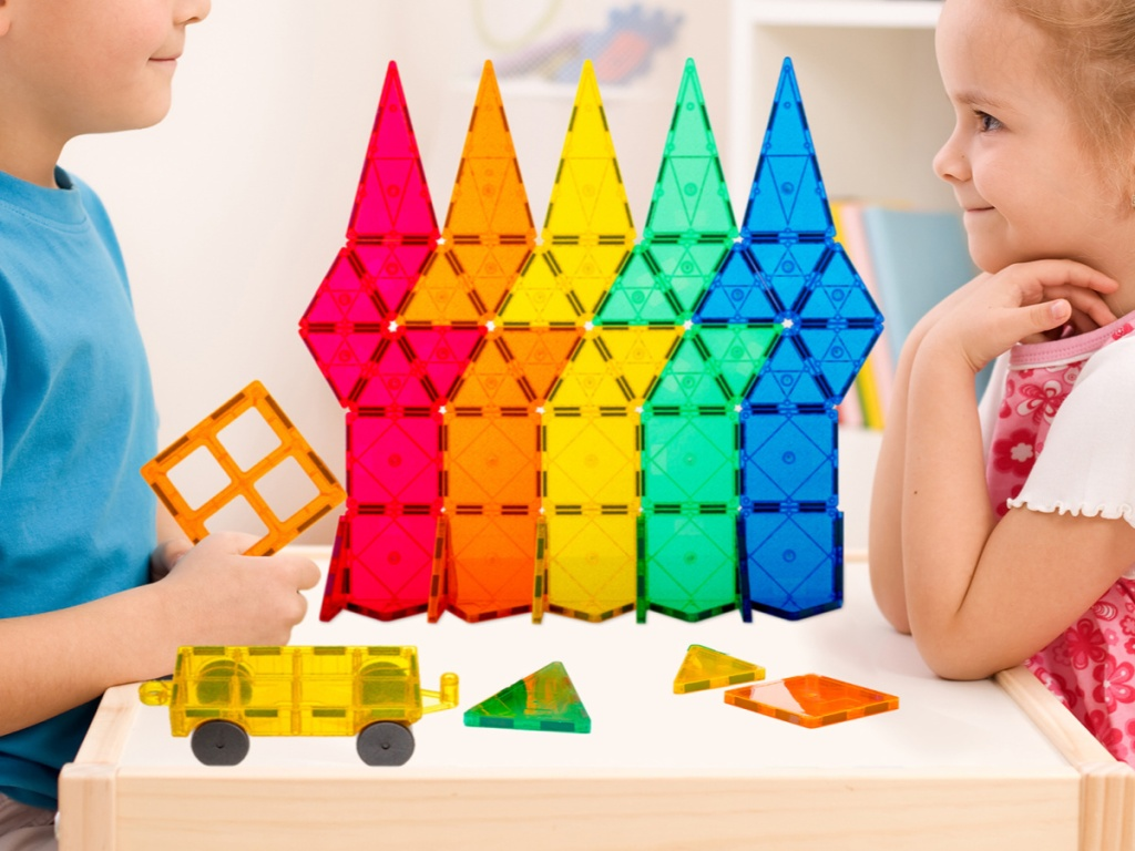 two kids playing with colorful toy building set on table