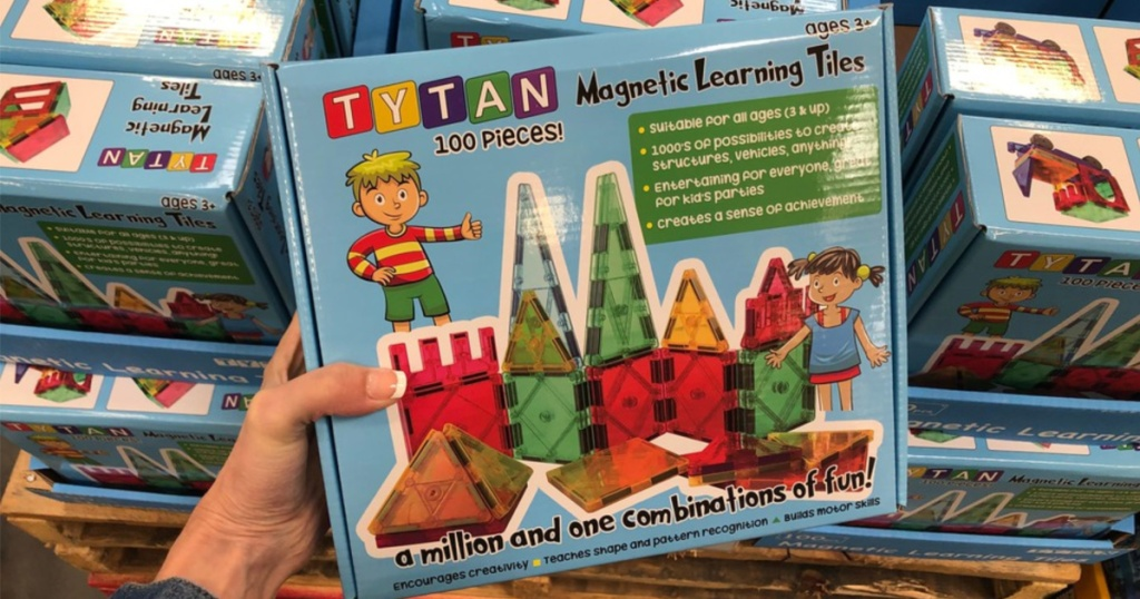 manicured hand holding toy building set in store