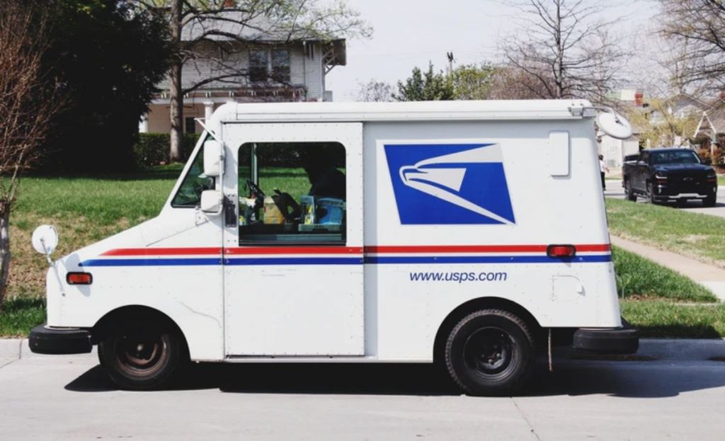 A USPS truck in front of a house