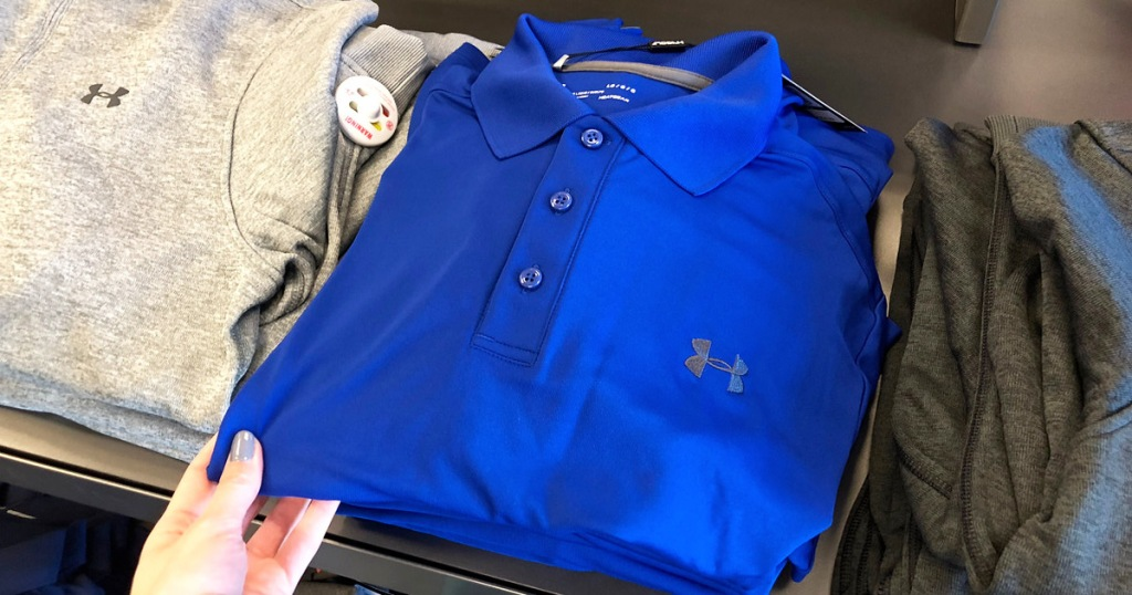 person holding a folded blue under armoud brand polo on a store display table