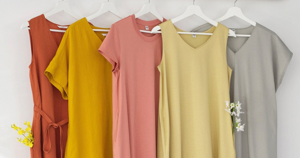 collection of womens dresses and shirts in solid colors hanging on white hangers