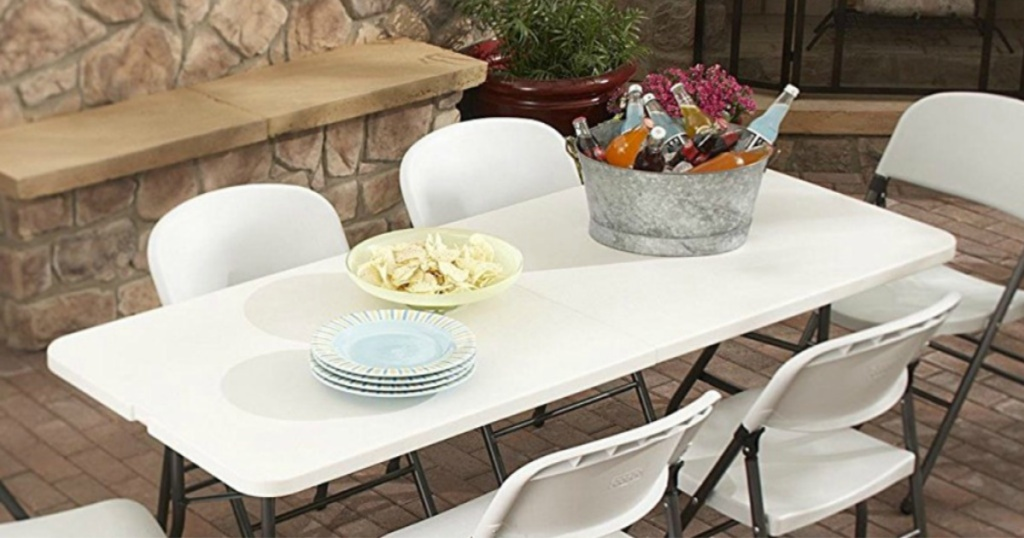 living accents fold inhalf rectangular table with white chairs all around