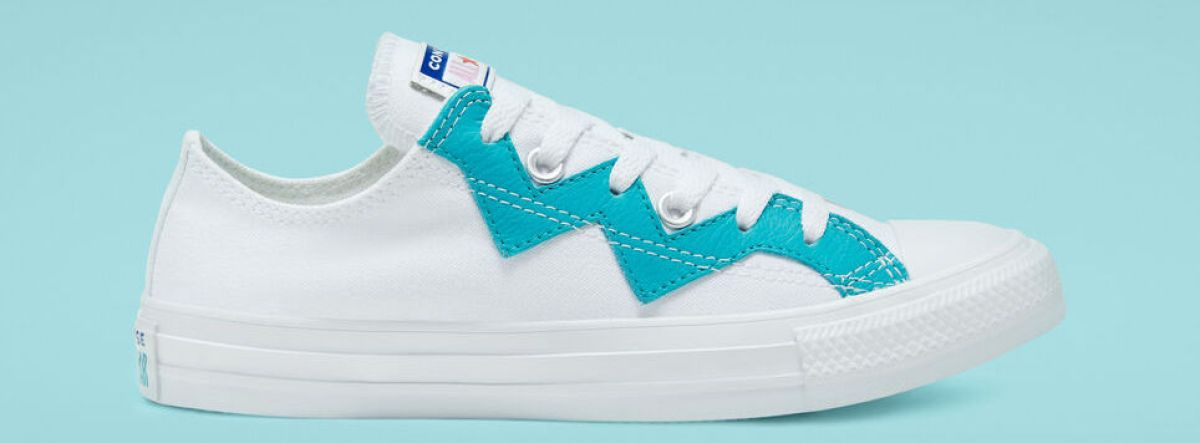 white Converse sneaker with blue trim on the top