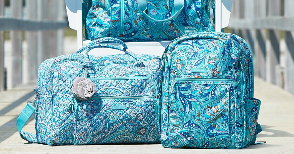 matching blue paisley print travel bag and backpack sitting on wooden dock