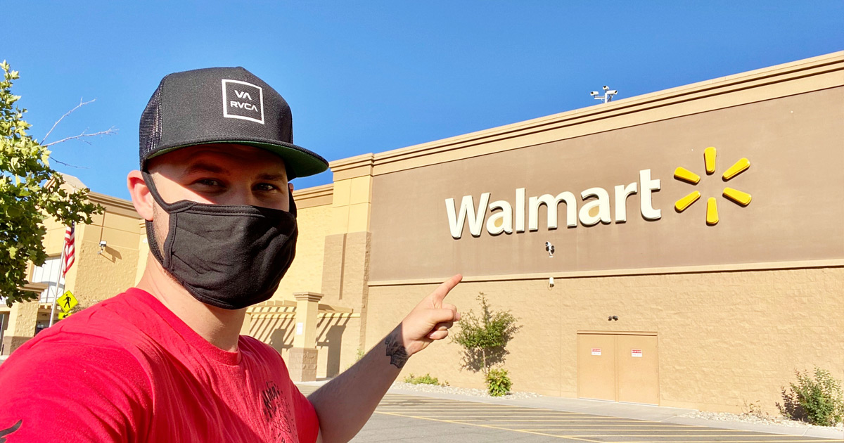 man in red shirt and black hat pointing at walmart sign while wearing black face mask