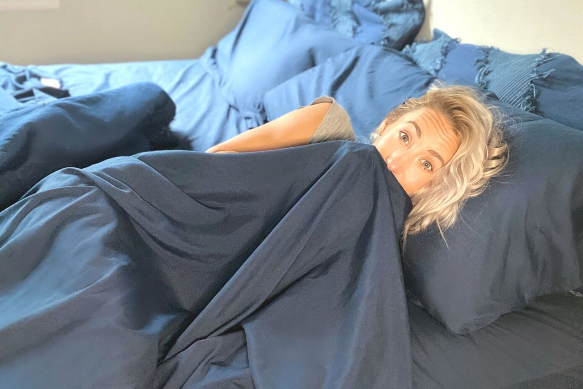 A woman laying in bed under some cozy sheets