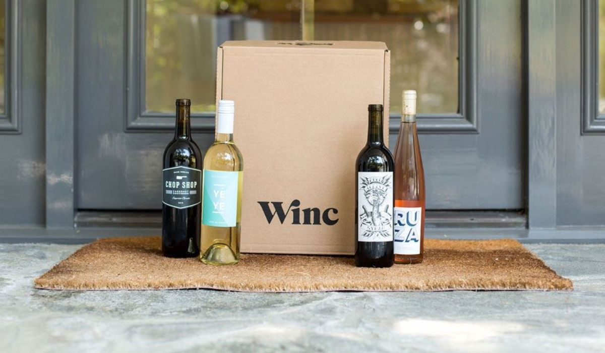 A wine subscription box on a porch next to wine bottles