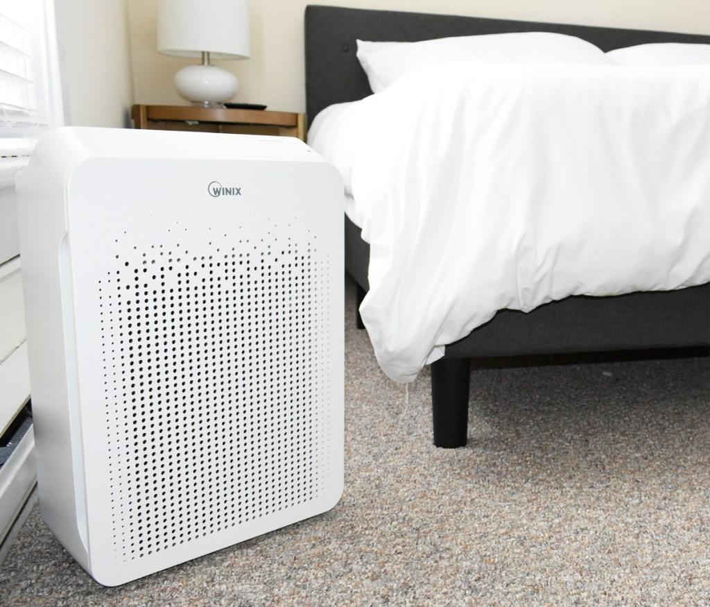 white rectangular air purifier on carpet in bedroom near bed