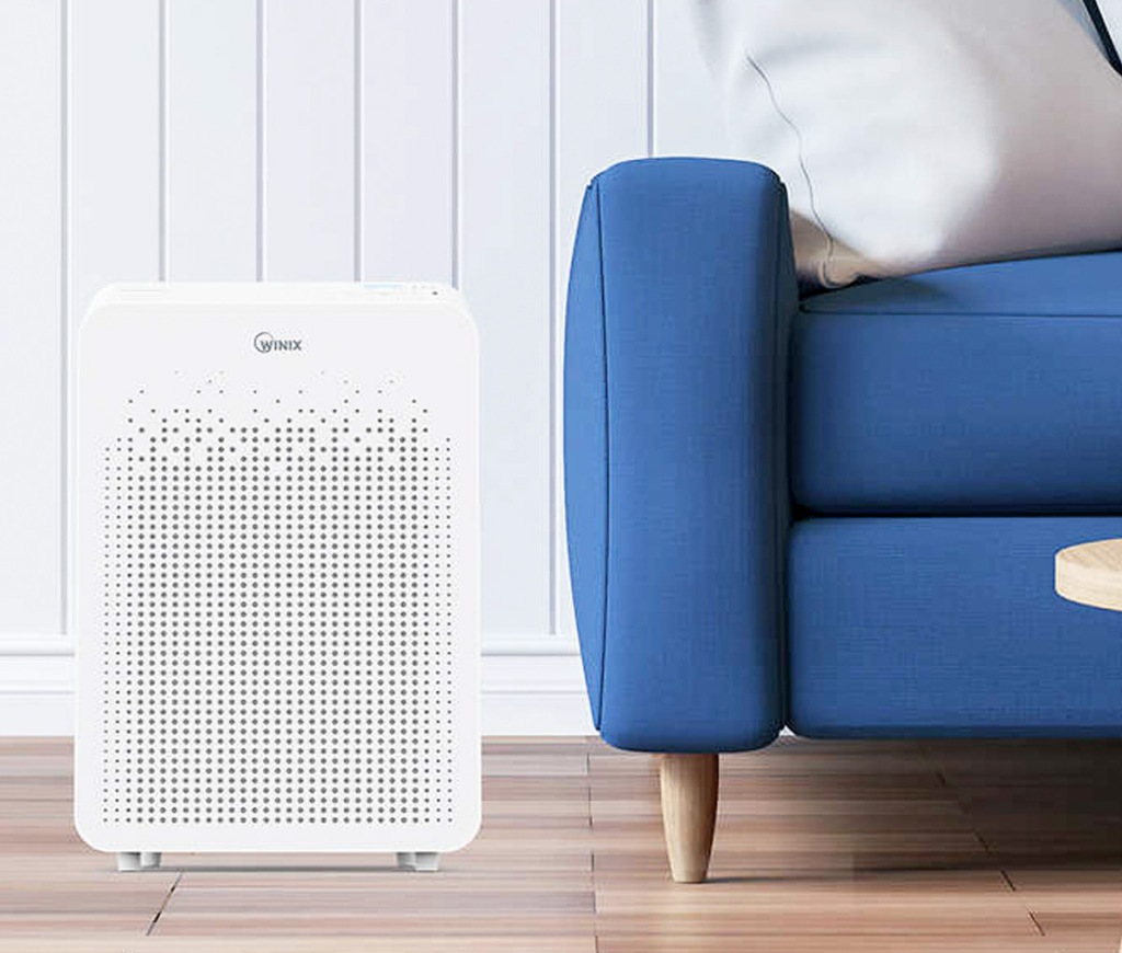 white air purifier on hardwood floor next to blue couch