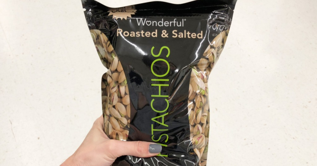 person with grey nails holding black bag os Wonderful roasted and salted pistachios
