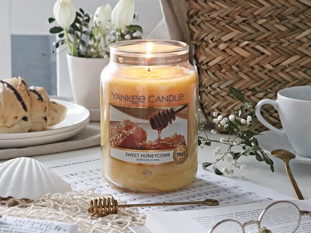 Yankee Candle Sweet Honeycomb scent next to cake, shell and glasses on a table