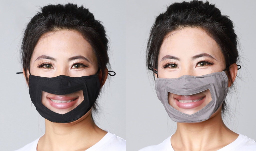 woman wearing black and gray and clear masks revealing her smile