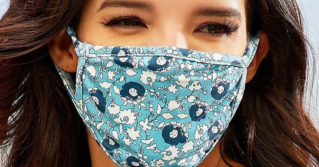 woman with dark brown hair wearing a light blue face mask with floral pattern on it