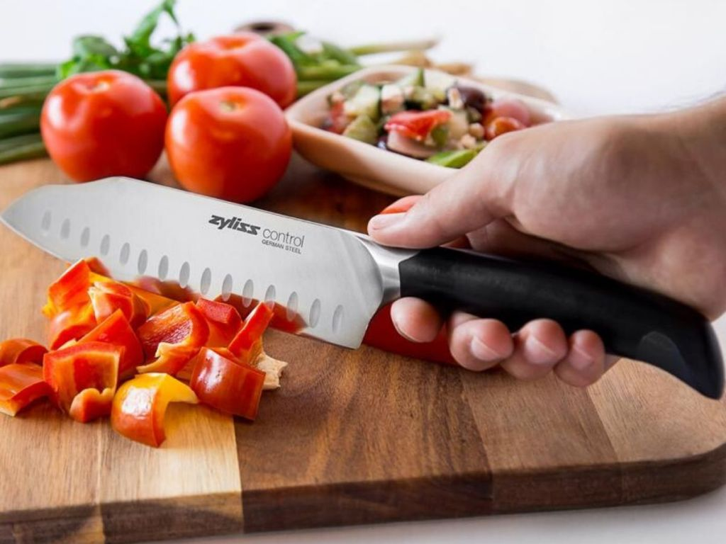 hand holding knife cutting tomatoes on a cutting board