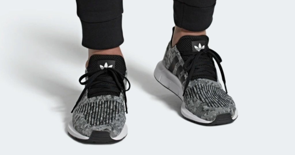 man wearing grey and black adidas running shoes