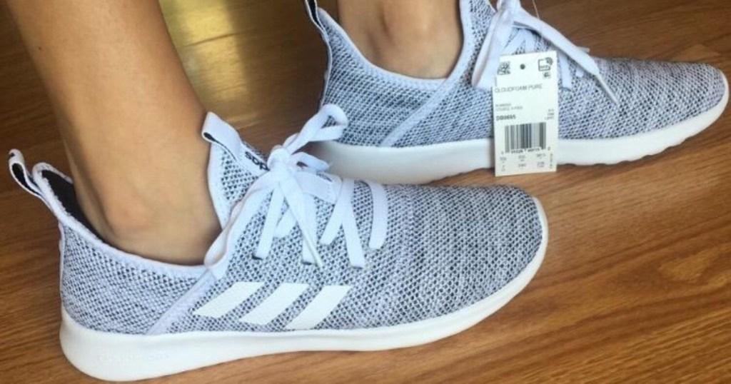 woman's feet in gray slip-on sneakers