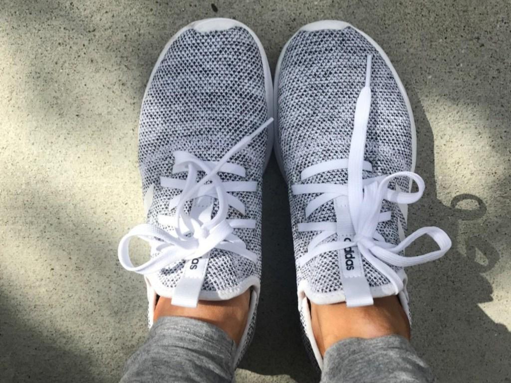 pair of feet in gray slip-on sneakers