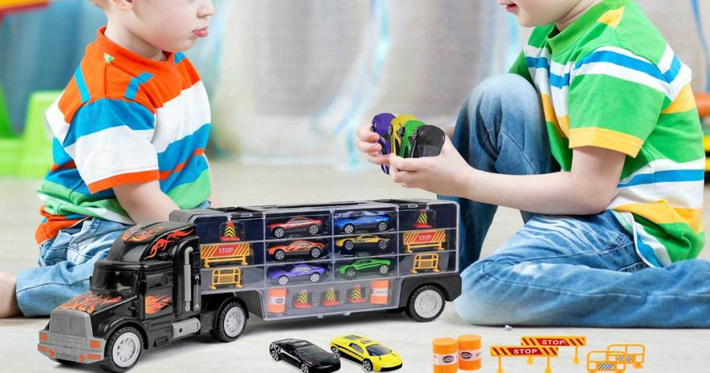 little boys playing with toy truck carrier and accessories