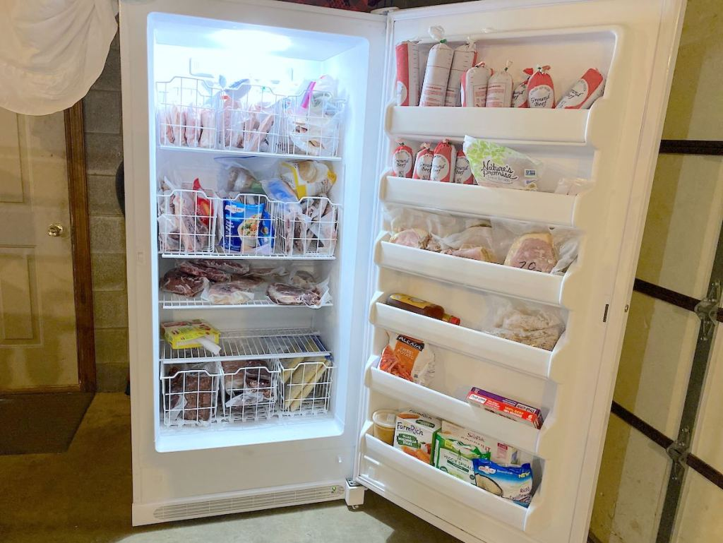 white stand up freezer in garage with various types of meat and food