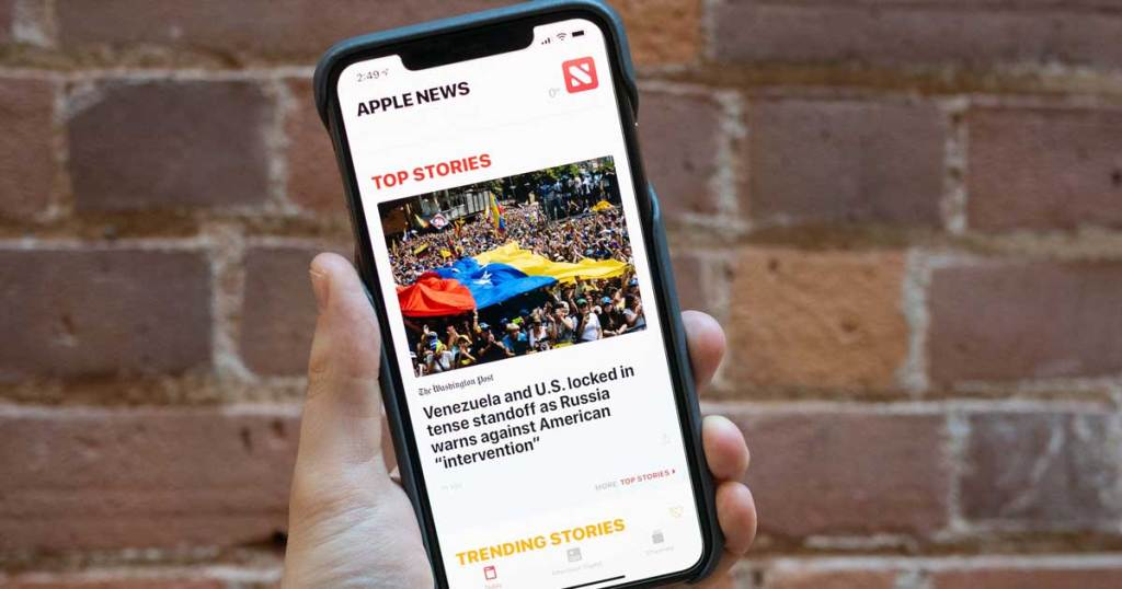 hand holding phone featuring apple news