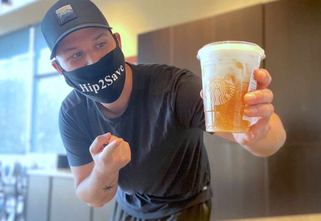 man wearing a hip2save mask holding a starbucks drink with half orange and white