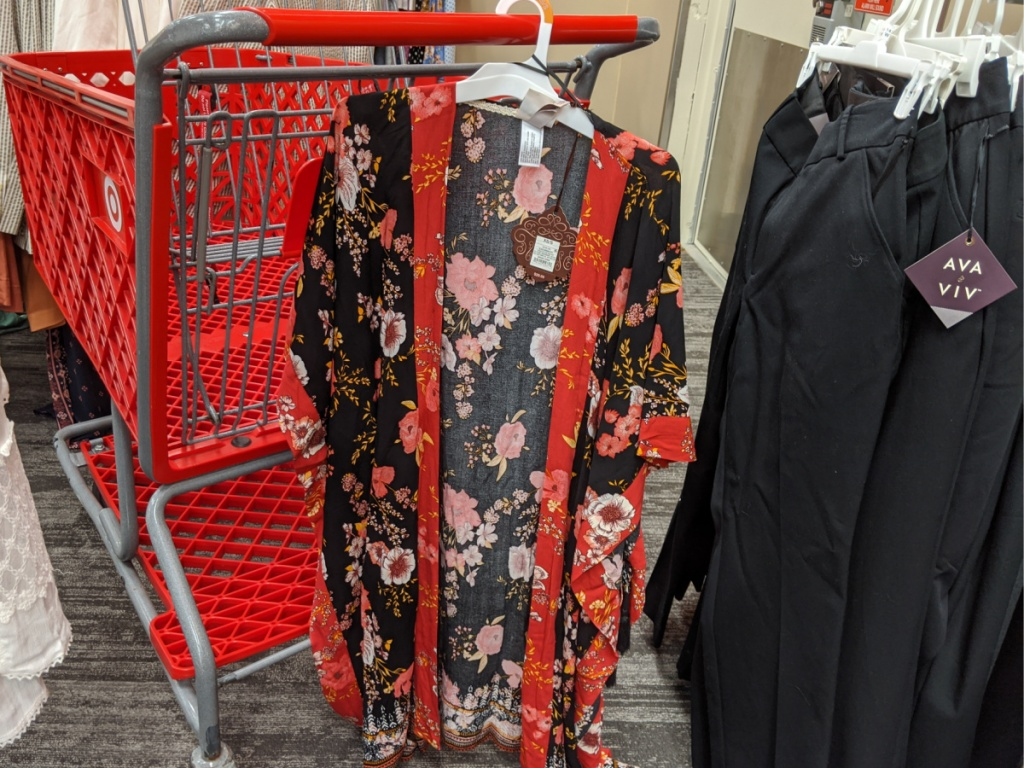 red grocery cart with woman's shirt hanging on it in store