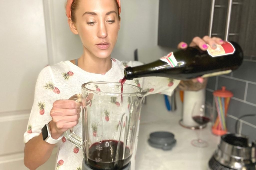 A woman pouring a bottle of wine in a blender