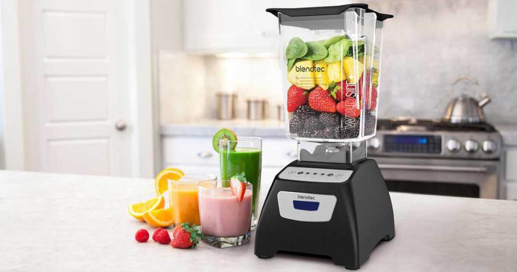 blender on a counter in a kitchen with smoothies