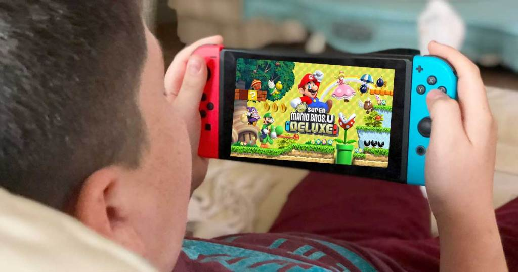 boy holding a nintendo switch and play mario bros