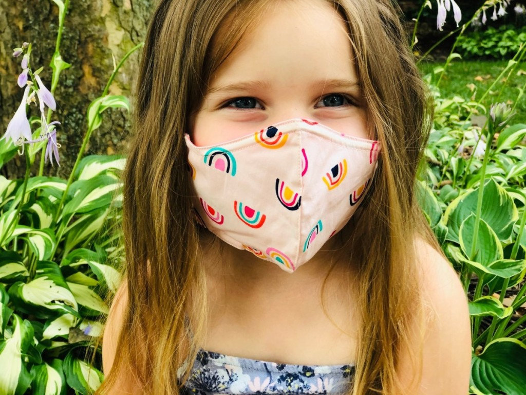 girl wearing pink mask with rainbows