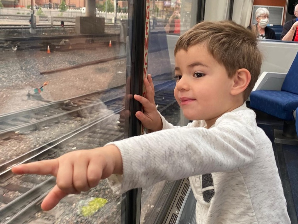 child pointing from train