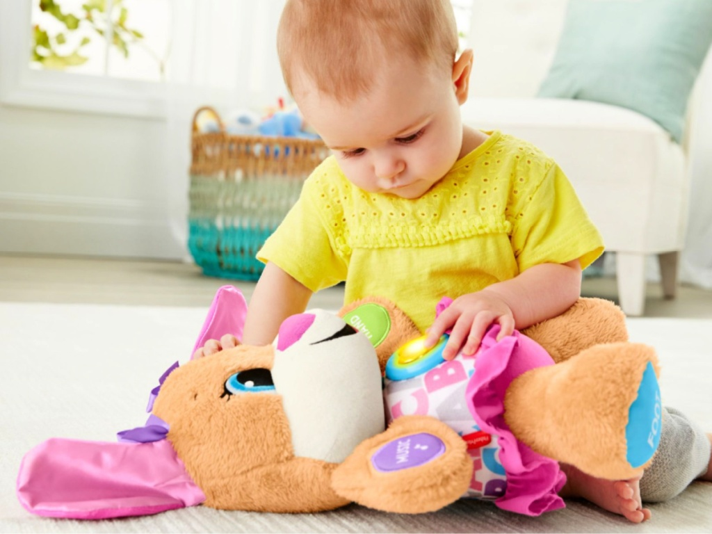 child holding a Fisher-Price Laugh & Learn Smart Stages Sis Plush Toy