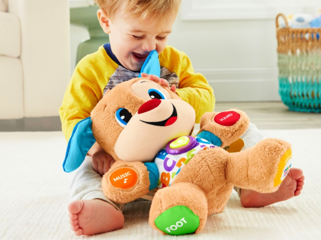 child holding a fisher price laugh and learn puppy