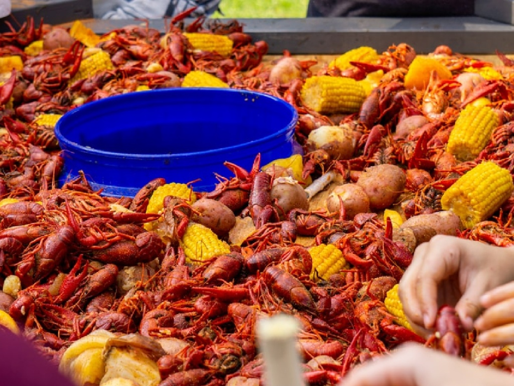 hands reaching into big batch of cooked crawfish and corn