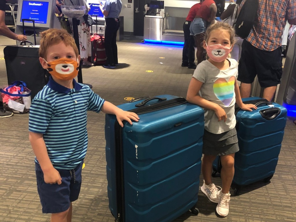 2 kids wearing animal face masks at the airport