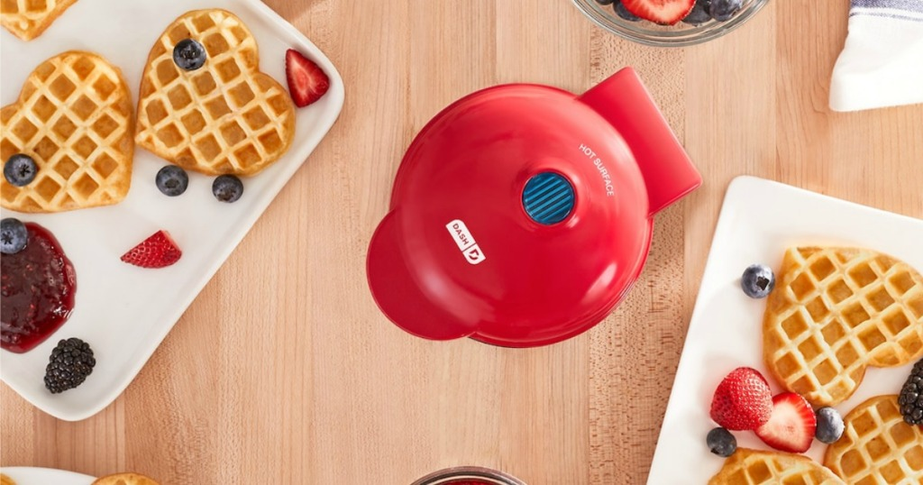 small red waffle maker and heart-shaped waffles with berries