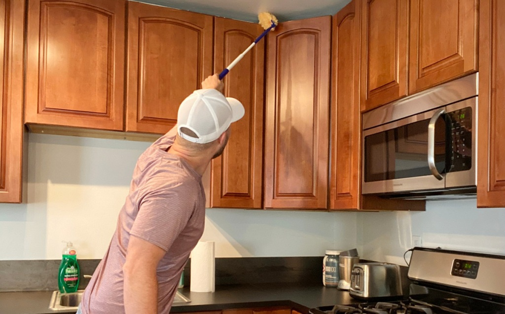 man dusting kitchen