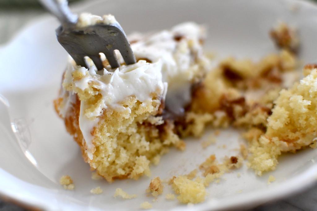 eating cinnamon roll poke cake with fork