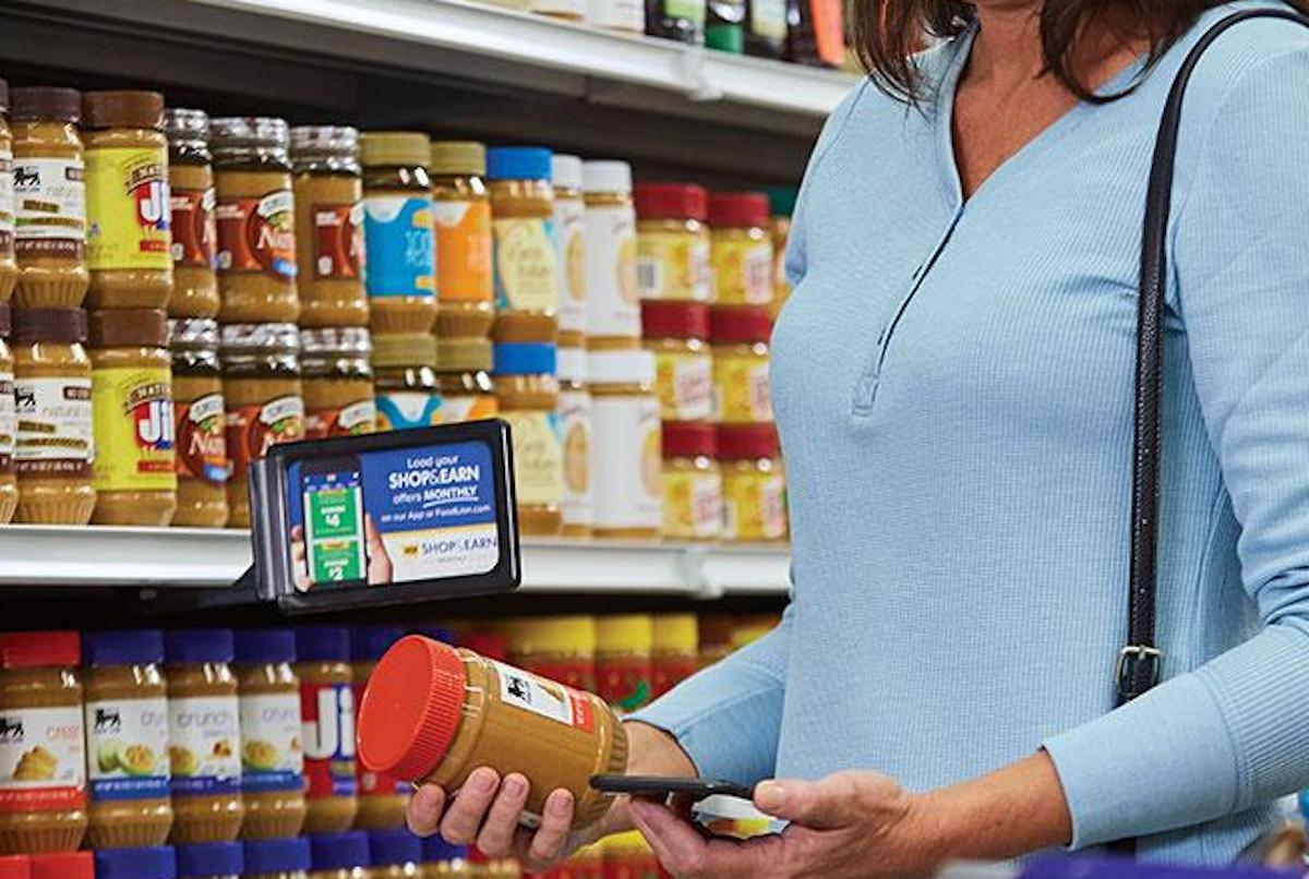 person holding jar of peanut butter in store aisle