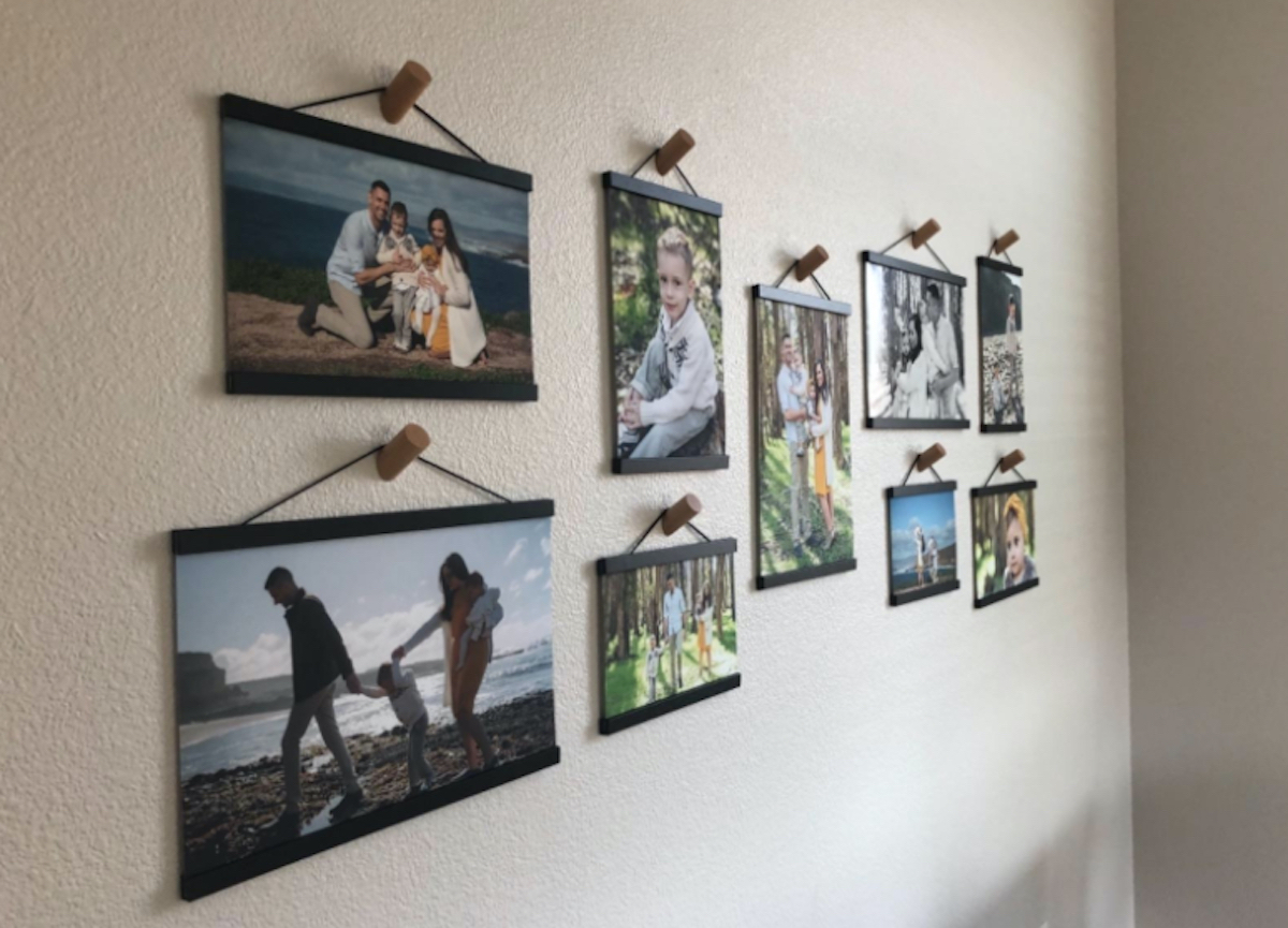 various sizes of family photos with wood frames hanging on hooks on walls