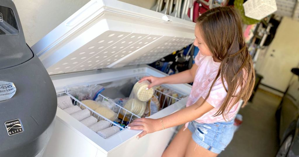 girl pulling frozen waffles out of a white freezer chest inside of garage