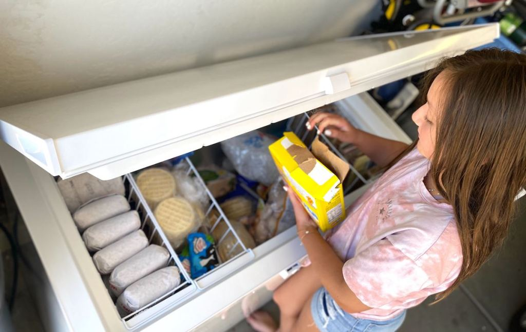 girl holding frozen box of food over stocked open best chest and upright freezer