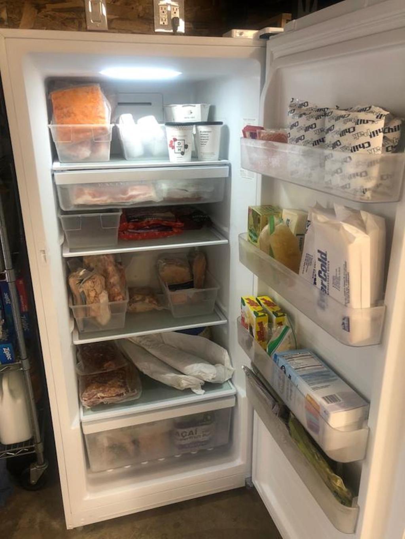 freezer sitting in garage with door open stocked full of food