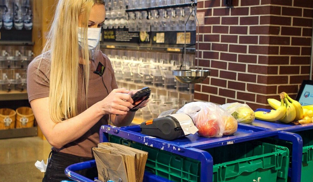 woman holding phone and wearing mask in grocery store
