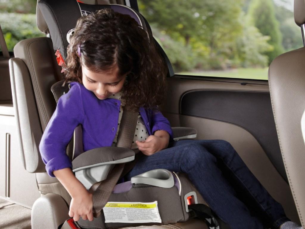 little girl buckling her seat belt sitting in booster